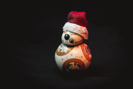 Lovely droid BB-8 from Star Wars, wearing a Christmas hat in dark background illuminated by colorful lights