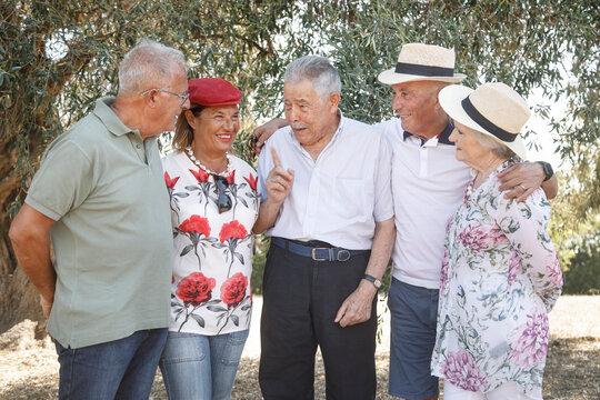 gruppo di anziani amici si abbracciano e si divertono in un parco