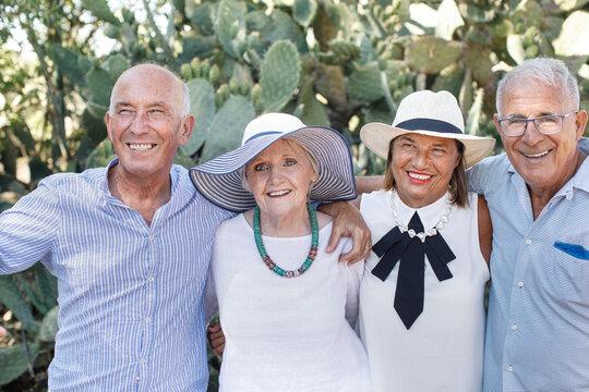 quattro anziani spensierati si abbracciano sorridenti in un parco