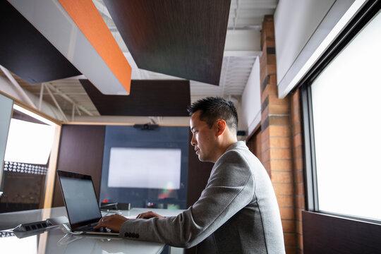 Businessman working on laptop by office window