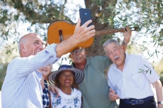 Gruppo di amici anziani si fa un selfie di gruppo in un parco