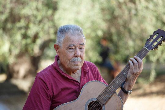 Uomo anziano suona malinconicamente una canzone con la chitarra in un parco