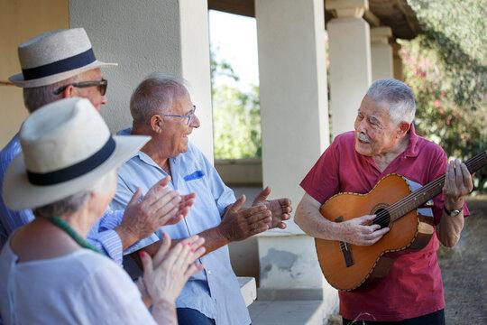 Gruppo di anziani vitali canta e suona con la chitarra una canzone seduti in una panchina