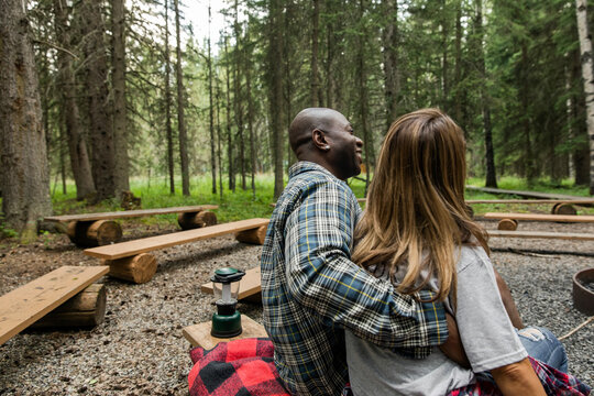 Couple sitting hugging in forest