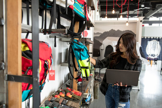 Female sporting goods store owner with laptop checking inventory
