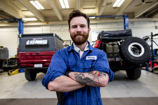 Portrait confident male auto mechanic with tattoos in custom garage