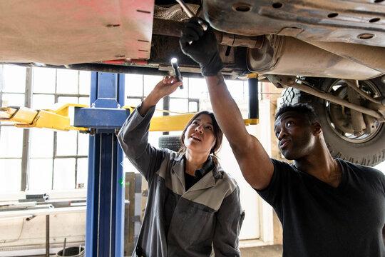 Auto mechanics with flashlight working under car on hydraulic lift