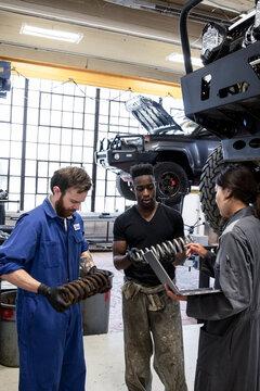 Auto mechanics with shocks working in garage