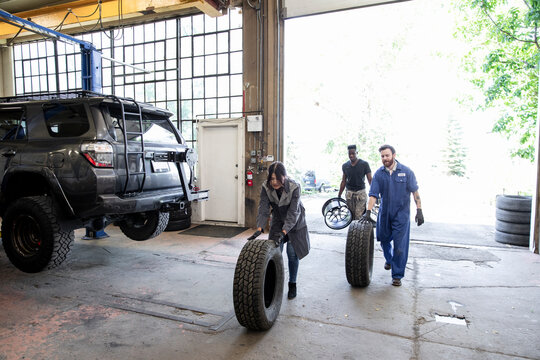 Auto mechanics rolling custom SUV tires into garage