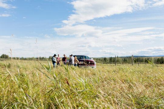 Farmers meeting at pickup truck in sunny field on vast rural farm