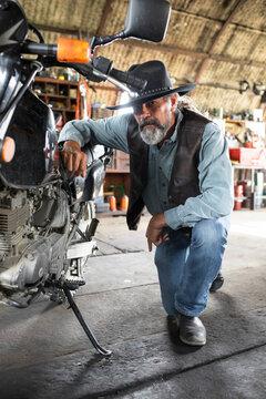 Portrait confident tough cowboy fixing motorcycle in barn workshop