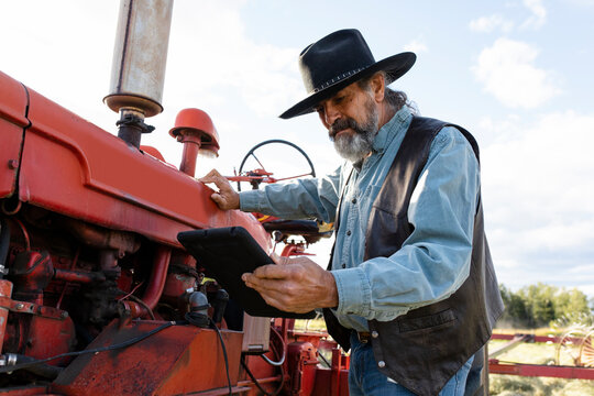 Male farmer in cowboy hat with digital tablet fixing tractor on farm