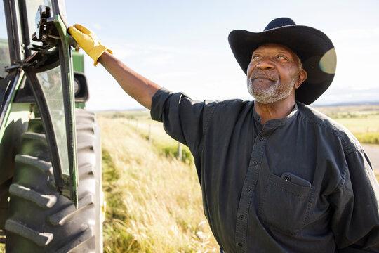 Portrait confident senior male farmer outside tractor in sunny field