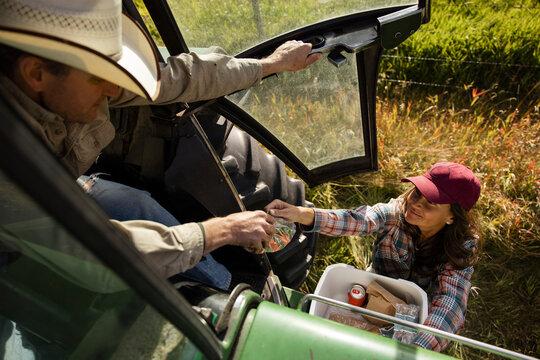 Female farmer bringing lunch to husband in tractor on sunny farm