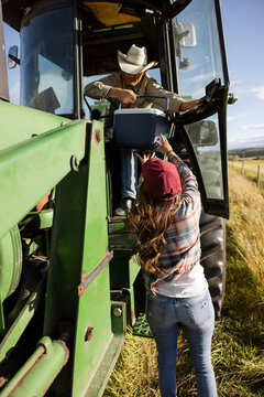 Female farmer bringing lunch to husband in tractor