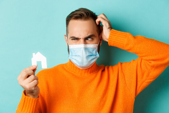 Real estate and coronavirus pandemic concept. Confused man in face mask scartching head while looking at small paper house, wearing orange sweater near light blue studio background