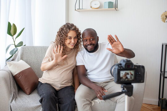 Modern family couple of bloggers broadcast for their channel, a pregnant curly woman and her dark-skinned husband waving their hands to their viewers. Pregnancy, family and video blogging concept.