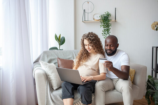 Future parents sitting on the sofa without leaving the house, order the necessary things in the maternity hospital, an African-American husband pays by credit card for Internet purchases.