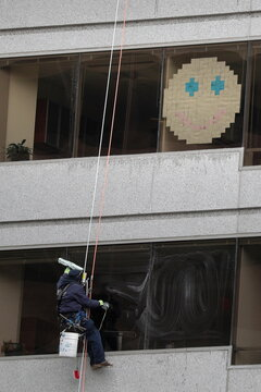 A window washer cleans an office building window below a smiling face made of Post-it notes near Franklin Square in Washington