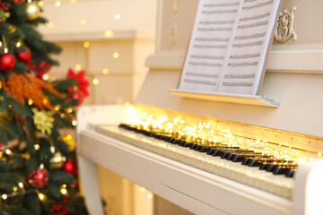 White piano with festive decor and note sheets indoors. Christmas music