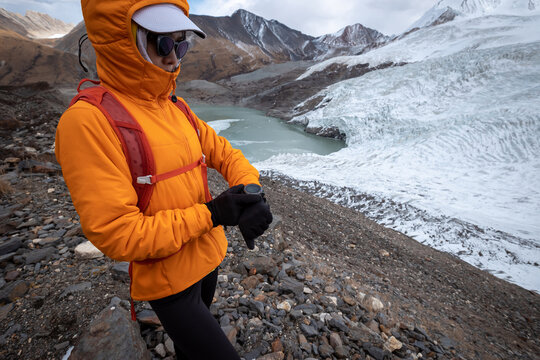 Woman hiker checking the altitude on sports watch on winter mountain top
