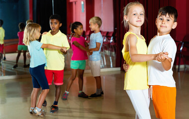 Group of positive smiling childrens trying dancing with partner in classroom