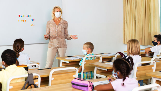 Young female teacher in protective face mask giving lesson to children in elementary school. New life reality during coronavirus pandemic