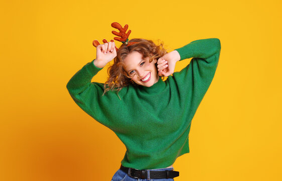 cheerful happy   woman  with  christmas deer antlers dances and enjoys life a colored yellow background.