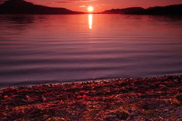 太陽の光に紅く染まる湖の風景。陽光の下のカルデラ湖の明媚な瞬間。