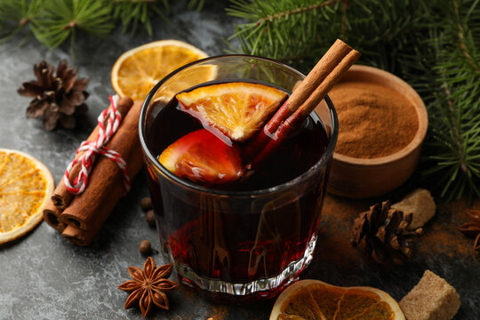 Glass of mulled wine and ingredients on black smokey background