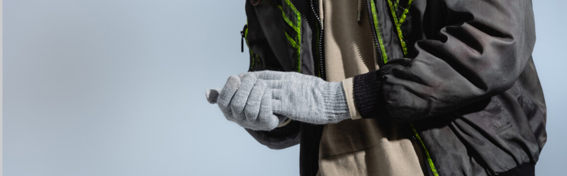 cropped view of man in anorak and gloves isolated on grey, banner