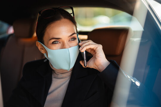 Pleased businesswoman wearing face mask talking on mobile phone in car