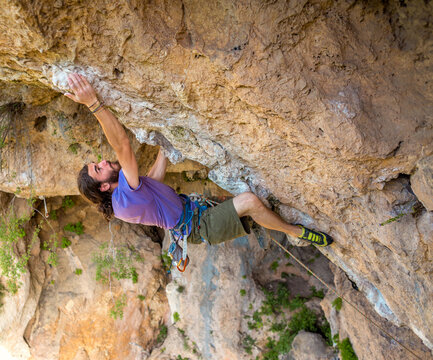 A strong man climbs a beautiful orange rock.
