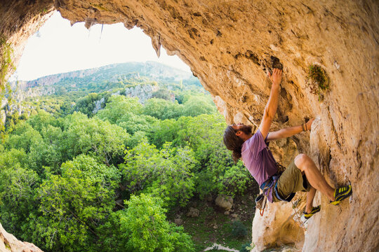 Rock climber climbs into the cave, Rock in the form of an arch
