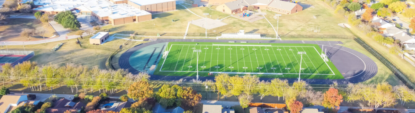 Panoramic top view school football field with running track, soccer goal, artificial playing surface and colorful autumn leaves near Dallas, Texas