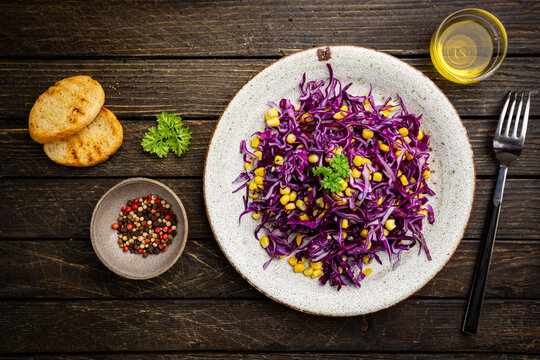 Fresh coleslaw salad made of shredded red and white cabbage and corn on dark wooden background, top view