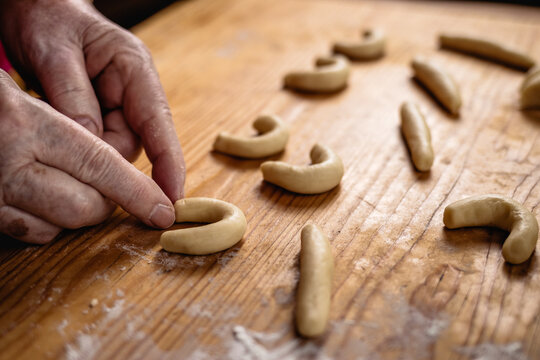 Baking vanillekipferl. Senior woman molding a vanilla crescent rolls from pastry dough. Making homemade traditional christmas cookies