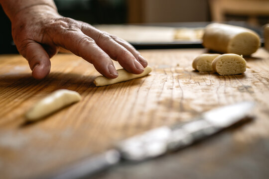 Rolling pastry dough by hand. Senior woman cooking small cookies on wooden board. Making traditional christmas sweet food