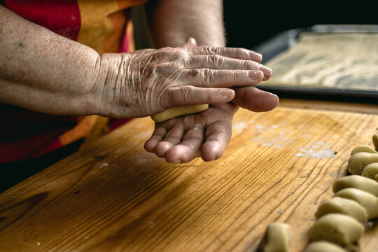 Grandmother cooking homemade cookies. Senior woman kneading pastry dough in hands