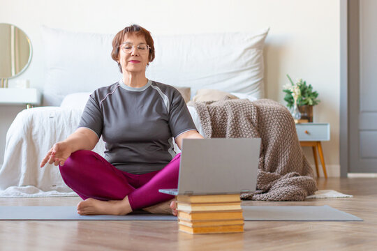 Senior woman meditates at home in a lotus position in front of a laptop monitor. The concept of a healthy lifestyle in old age.
