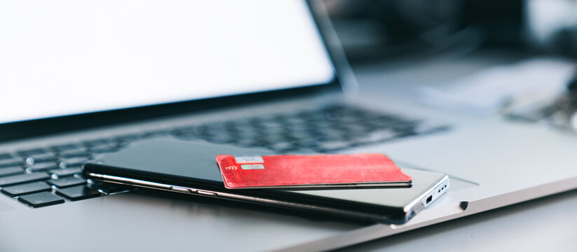 Credit card for shopping online with modern laptop and smartphone. Online payment for purchases from online stores, close up view. Mobile payment, e-commerce, gift card, technology, spending money.