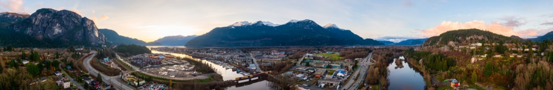 Aerial Panoramic View of Residential Homes, Sea to Sky Highway and Shopping Mall. Colorful Sunset Sky. Taken in Squamish, North of Vancouver, British Columbia, Canada.