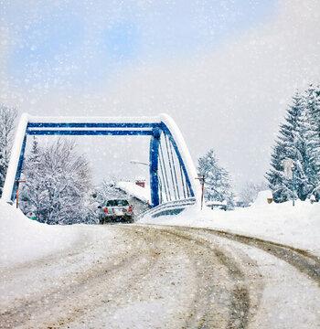 Austria, after heavy snowfall a car drives carefully on a bridge