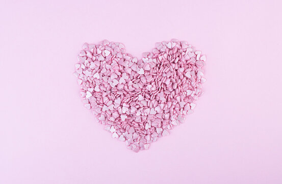Hundreds of tiny pink heart-shaped hearts lie in the shape of a large heart as a symbol of romantic love