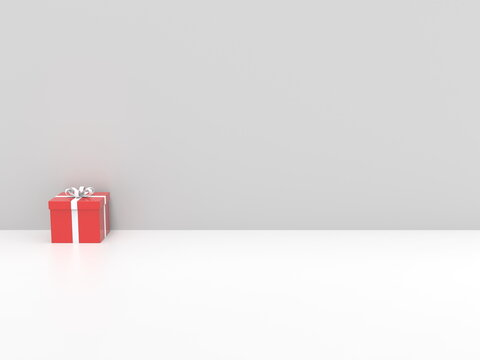 Red Christmas gift box with white ribbon - on white background against white wall