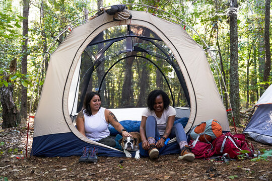 Diverse female friends camping in tent in the woods