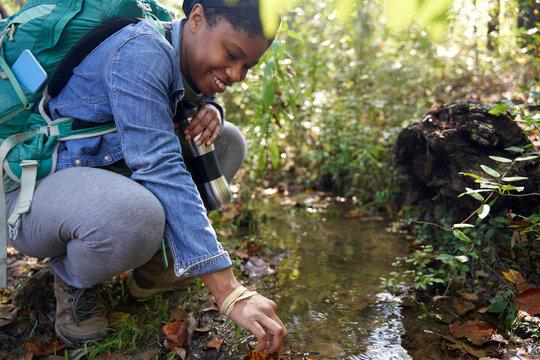 Black female botanist examines plants on trail