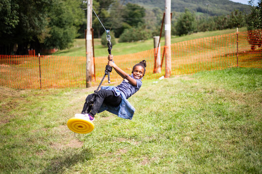 Young black girl playing outdoors on homemade swing