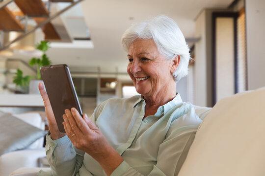 Happy senior caucasian woman having video call using tablet