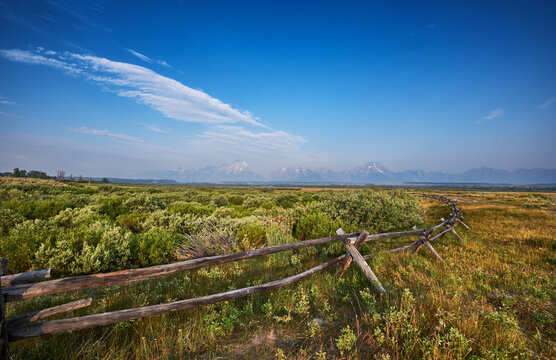 Old fashioned split rail wooden fence on the land of Cunningham Ranch, Moose, Wyoming. Teton mountains in the distance to the West